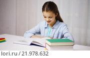 Купить «happy school girl reading book or textbook at home», видеоролик № 21978632, снято 12 декабря 2015 г. (c) Syda Productions / Фотобанк Лори