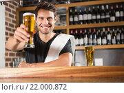 Купить «Handsome barman holding a pint of beer», фото № 22000872, снято 24 октября 2015 г. (c) Wavebreak Media / Фотобанк Лори