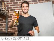Купить «Handsome man holding a pint of beer», фото № 22001132, снято 24 октября 2015 г. (c) Wavebreak Media / Фотобанк Лори