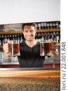 Купить «Handsome barman holding a pint of beer», фото № 22001848, снято 24 октября 2015 г. (c) Wavebreak Media / Фотобанк Лори