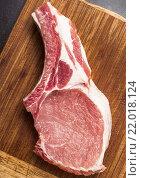 Сочный кусок мяса на кости лежит на деревянном столе. Стоковое фото, фотограф Riasna Yuliia / Фотобанк Лори