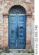 Купить «Синяя деревянная дверь с аркой в старой каменной стене», фото № 22050740, снято 11 февраля 2016 г. (c) EugeneSergeev / Фотобанк Лори