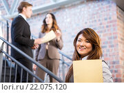 Купить «Businesswoman standing near staircase with documents», фото № 22075120, снято 18 октября 2015 г. (c) Wavebreak Media / Фотобанк Лори