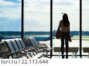 Купить «Силуэт пассажирки, ожидающей рейс в аэропорту», фото № 22113644, снято 10 июня 2015 г. (c) Дмитрий Травников / Фотобанк Лори