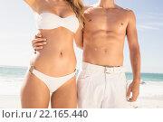 Купить «Young couple in beachwear embracing», фото № 22165440, снято 12 ноября 2015 г. (c) Wavebreak Media / Фотобанк Лори