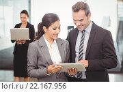Купить «Businessman and businesswoman using digital tablet», фото № 22167956, снято 31 октября 2015 г. (c) Wavebreak Media / Фотобанк Лори