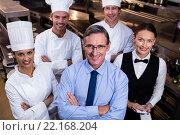 Купить «Happy restaurant team standing together with arms crossed in commercial kitchen», фото № 22168204, снято 23 ноября 2015 г. (c) Wavebreak Media / Фотобанк Лори