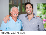 Купить «Portrait of smiling father and son with arm around», фото № 22173896, снято 6 ноября 2015 г. (c) Wavebreak Media / Фотобанк Лори