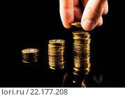Рука складывает стопки монет на черном фоне. Стоковое фото, фотограф Александр Рыбин / Фотобанк Лори