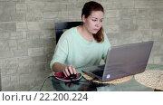 Купить «Симпатичная сосредоточенная женщина сидит на кухне за стеклянным столом и работает на ноутбуке», видеоролик № 22200224, снято 15 марта 2016 г. (c) Кекяляйнен Андрей / Фотобанк Лори