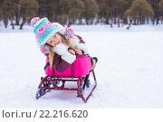 Купить «Девочка на санях зимой в снежный день», фото № 22216620, снято 18 января 2015 г. (c) Дмитрий Травников / Фотобанк Лори