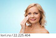 Купить «happy woman cleaning face with cotton pad», фото № 22225404, снято 27 ноября 2015 г. (c) Syda Productions / Фотобанк Лори