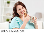 Купить «happy plus size woman with cup and cookie at home», фото № 22225760, снято 21 февраля 2016 г. (c) Syda Productions / Фотобанк Лори