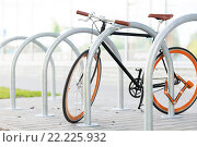 Купить «close up of bicycle locked at street parking», фото № 22225932, снято 30 мая 2015 г. (c) Syda Productions / Фотобанк Лори