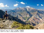 Купить «Велосипедист стоит на скале и наслаждается видом на горы», фото № 22226180, снято 17 октября 2012 г. (c) Евгений Дубинчук / Фотобанк Лори