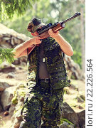 Купить «soldier or hunter shooting with gun in forest», фото № 22226564, снято 14 августа 2014 г. (c) Syda Productions / Фотобанк Лори