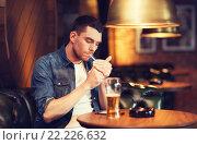 Купить «man drinking beer and smoking cigarette at bar», фото № 22226632, снято 22 апреля 2015 г. (c) Syda Productions / Фотобанк Лори