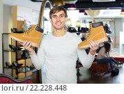 Купить «Young man in a shoe store», фото № 22228448, снято 17 июня 2019 г. (c) Яков Филимонов / Фотобанк Лори