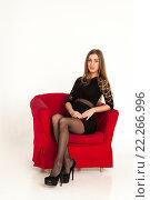 Купить «Молодая девушка в чёрном платье сидит в красном кресле», фото № 22266996, снято 16 января 2016 г. (c) Литвяк Игорь / Фотобанк Лори