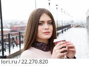 Купить «Молодая девушка пьет кофе на улице в ненастную погоду», фото № 22270820, снято 20 марта 2016 г. (c) Момотюк Сергей / Фотобанк Лори