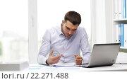 Купить «busy businessman with laptop and papers in office», видеоролик № 22271488, снято 9 июля 2015 г. (c) Syda Productions / Фотобанк Лори