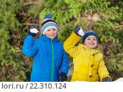 Купить «Два маленьких мальчика играют в снежки в лесу», фото № 22310124, снято 31 января 2016 г. (c) Сергей Новиков / Фотобанк Лори