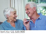 Купить «Happy senior couple listening to music through phone», фото № 22320900, снято 29 ноября 2015 г. (c) Wavebreak Media / Фотобанк Лори