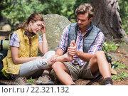 Man massaging leg of woman while sitting on field. Стоковое фото, агентство Wavebreak Media / Фотобанк Лори