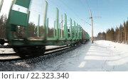 Купить «Товарные вагоны электропоезда проезжают по зимней железной дороге в лесу», видеоролик № 22323340, снято 21 марта 2016 г. (c) Кекяляйнен Андрей / Фотобанк Лори