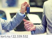 Купить «close up of male hands with car key in auto salon», фото № 22339532, снято 22 января 2015 г. (c) Syda Productions / Фотобанк Лори