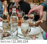 Купить «Мужчина за столом наливает шампанское в бокал», эксклюзивное фото № 22360224, снято 12 июля 2015 г. (c) Игорь Низов / Фотобанк Лори
