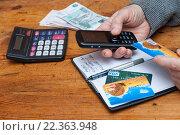 Телефон и платежная карта в руках пенсионера (2016 год). Редакционное фото, фотограф Короленко Елена / Фотобанк Лори