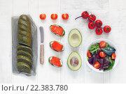 Вид сверху на багет, бутерброды с красной рыбой, авокадо и салат из свежих овощей. Стоковое фото, фотограф Козлова Анастасия / Фотобанк Лори