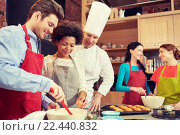 Купить «happy friends and chef cook baking in kitchen», фото № 22440832, снято 12 февраля 2015 г. (c) Syda Productions / Фотобанк Лори