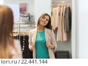 Купить «happy woman posing at mirror in clothing store», фото № 22441144, снято 19 февраля 2016 г. (c) Syda Productions / Фотобанк Лори