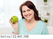 Купить «happy plus size woman eating green apple at home», фото № 22441188, снято 21 февраля 2016 г. (c) Syda Productions / Фотобанк Лори