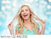 Купить «smiling young woman holding her strand of hair», фото № 22442032, снято 13 февраля 2016 г. (c) Syda Productions / Фотобанк Лори