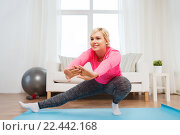 Купить «happy woman stretching leg on mat at home», фото № 22442168, снято 7 февраля 2016 г. (c) Syda Productions / Фотобанк Лори