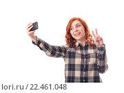 Купить «Радостная рыжеволосая девушка фотографирует себя на мобильный телефон», фото № 22461048, снято 30 мая 2020 г. (c) Максим Бейков / Фотобанк Лори