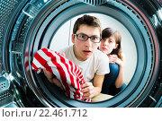 Купить «Молодая пара загружает одежду в стиральную машину», фото № 22461712, снято 5 июня 2020 г. (c) Кузнецов Дмитрий / Фотобанк Лори