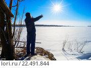 Купить «Подросток стоит на берегу замерзшей реки и тянет руки к солнцу», фото № 22491844, снято 27 марта 2016 г. (c) Алексей Маринченко / Фотобанк Лори