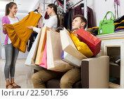 Купить «Девушка покупает платье в магазине, мужчина сидит с пакетами покупок», фото № 22501756, снято 17 июля 2018 г. (c) Татьяна Яцевич / Фотобанк Лори