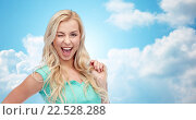 Купить «smiling young woman holding her strand of hair», фото № 22528288, снято 13 февраля 2016 г. (c) Syda Productions / Фотобанк Лори