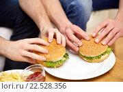 Купить «close up of male hands with hamburgers on table», фото № 22528356, снято 22 марта 2014 г. (c) Syda Productions / Фотобанк Лори