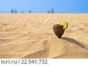 Экзотический коктейль с кусочком лайма в половине кокоса, стоящий в песке на пляже. Стоковое фото, фотограф Алексей Безрук / Фотобанк Лори