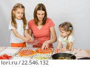Старшая дочка помогает маме готовить пиццу, а младшая наблюдает за ними. Стоковое фото, фотограф Иванов Алексей / Фотобанк Лори