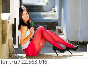 Attractive young woman with a rose flower in hand. Стоковое фото, фотограф Emil Pozar / age Fotostock / Фотобанк Лори