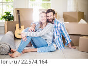 Купить «Portrait of smiling couple sitting on floor», фото № 22574164, снято 20 января 2016 г. (c) Wavebreak Media / Фотобанк Лори