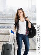 Девушка стоит с чемоданом, паспортом и билетом (2016 год). Редакционное фото, фотограф Riasna Yuliia / Фотобанк Лори