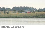 Купить «Дым от пожара в лагере и автомобили на берегу реки», видеоролик № 22593376, снято 30 сентября 2015 г. (c) Валерий Гусак / Фотобанк Лори
